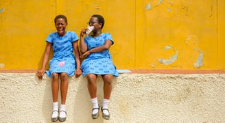 Ghana kinderdorp Tema twee vriendinnen lachend bij hun school