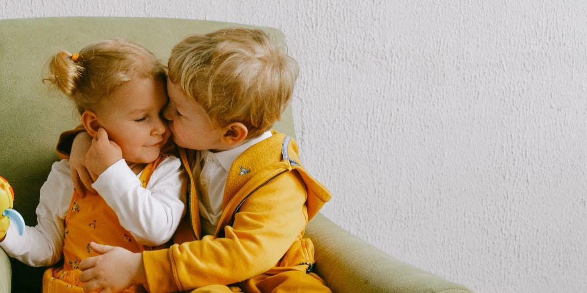 Broertje en zusje knuffelen op bank